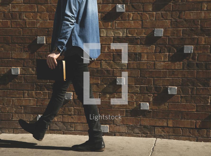 A man walking on sidewalk carrying a Bible