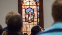 parishioners and a stained glass window of Jesus the good shepherd