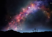Three crosses on a hill under the starry night sky.