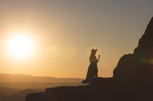 a silhouette of a woman in a hat on a mountains edge