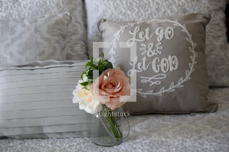 flowers and a Let Go and Let God throw pillow on a bed