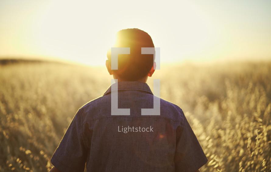 a young man walking through a field of tall grass at sunset