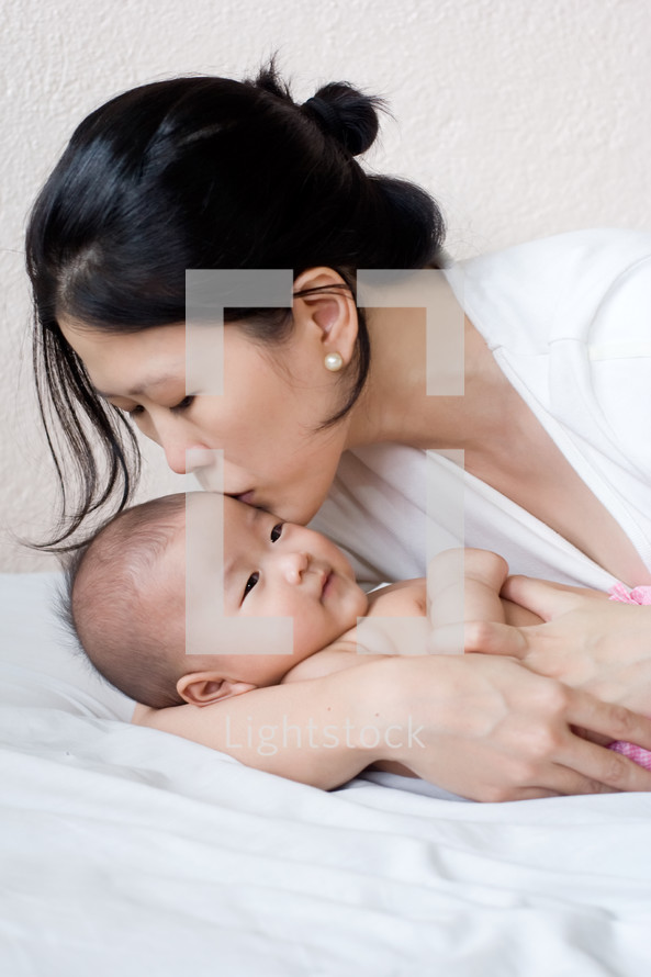 An Asian mother kissing her newborn baby