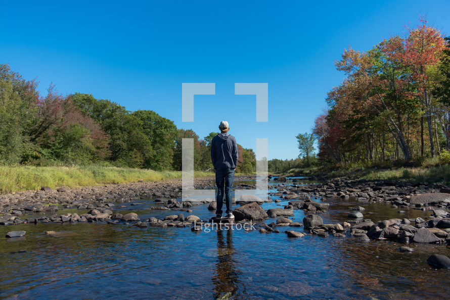 young man standing on rocks in a river