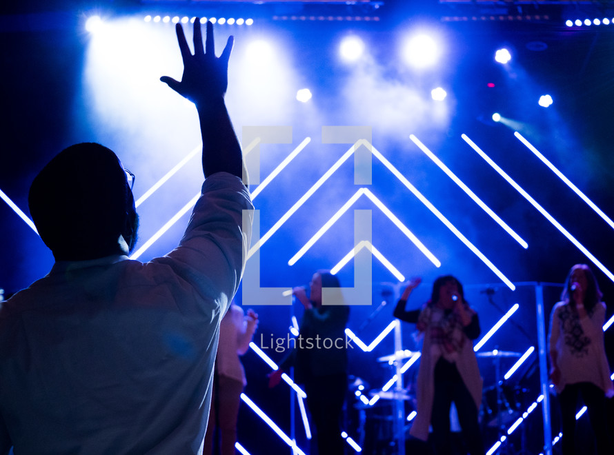 raised hands in the audience at a concert