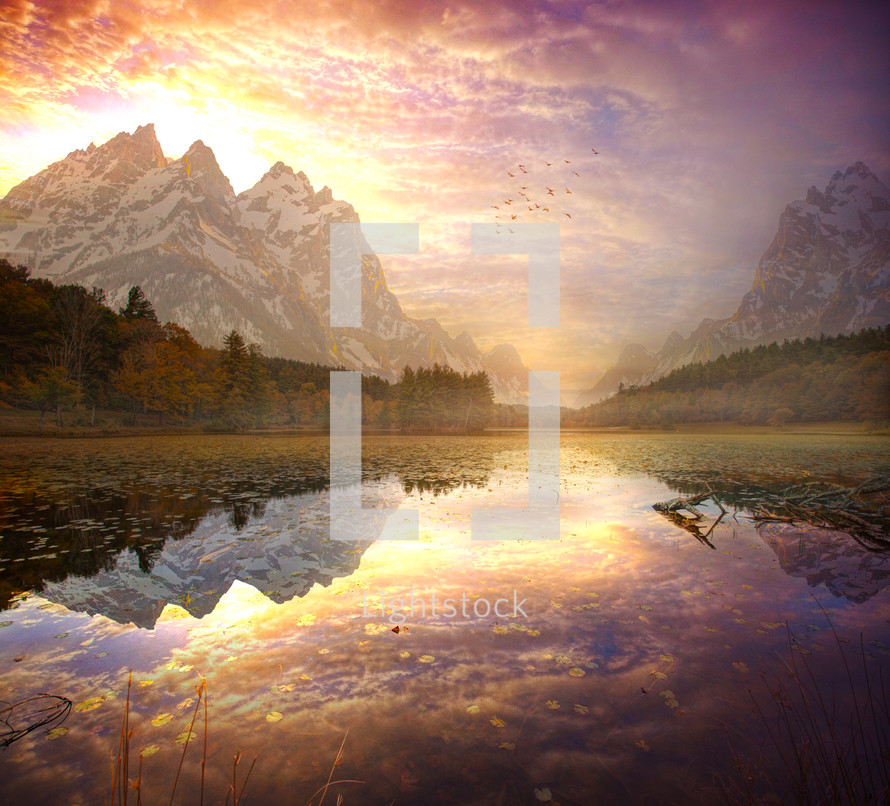 A beautiful sunrise over the tall mountains with a lake reflection