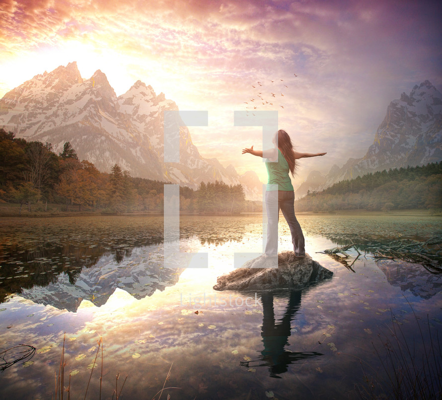 A woman stands in awe and worship during a beautiful sunrise