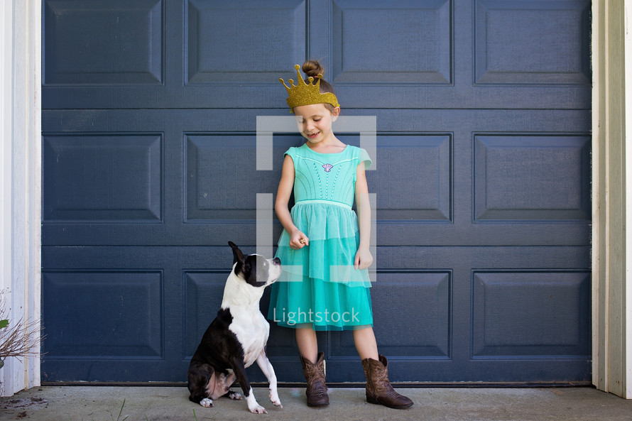 a girl standing in front of her garage with her dog