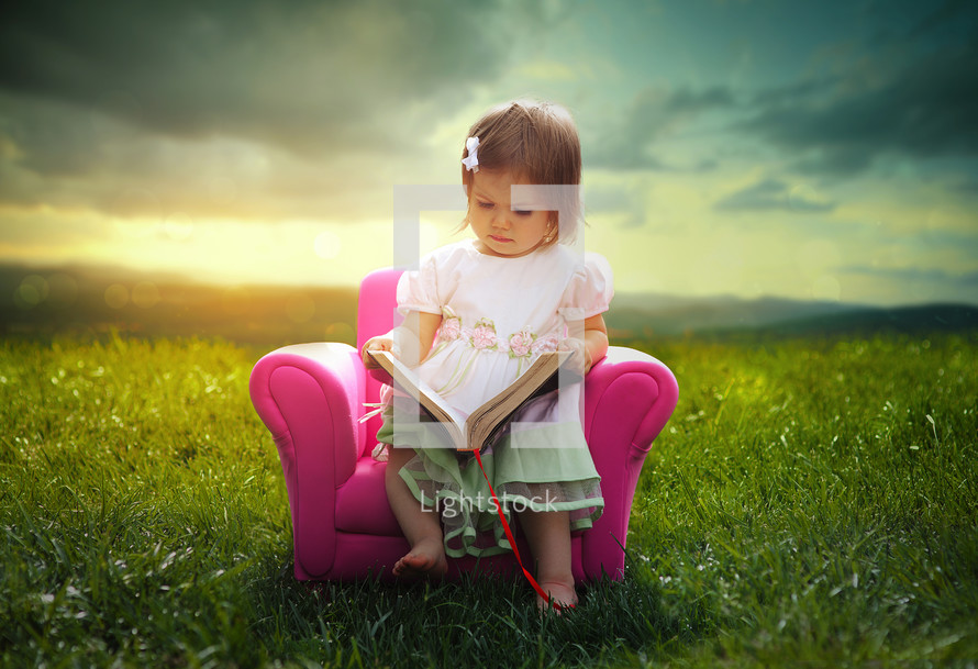 a little girl reading a Bible in a pink chair outdoors