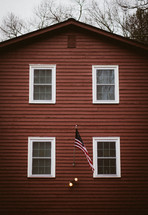 American flag on the side of a red house