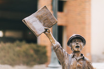 statue of a boy holding up a newspaper
