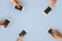 Five hands with cell phones on a blue surface.