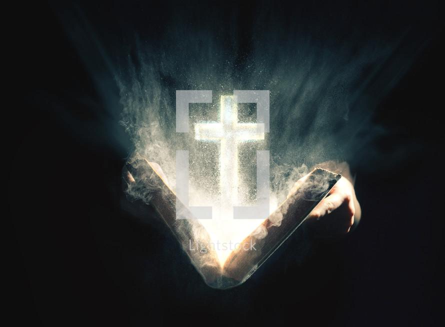 An illuminated cross rising from an open Bible.