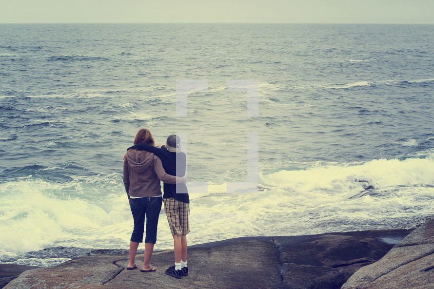 mother and son looking out at the ocean