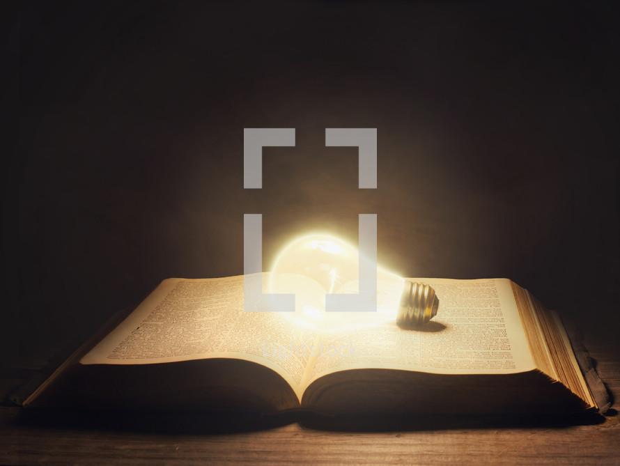 glowing lightbulb on an open Bible
