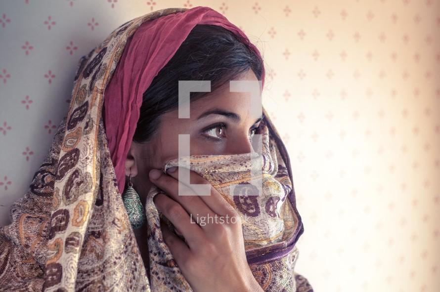 Middle eastern women revealing her eyes and covering the lower part o fher face with her shawl.