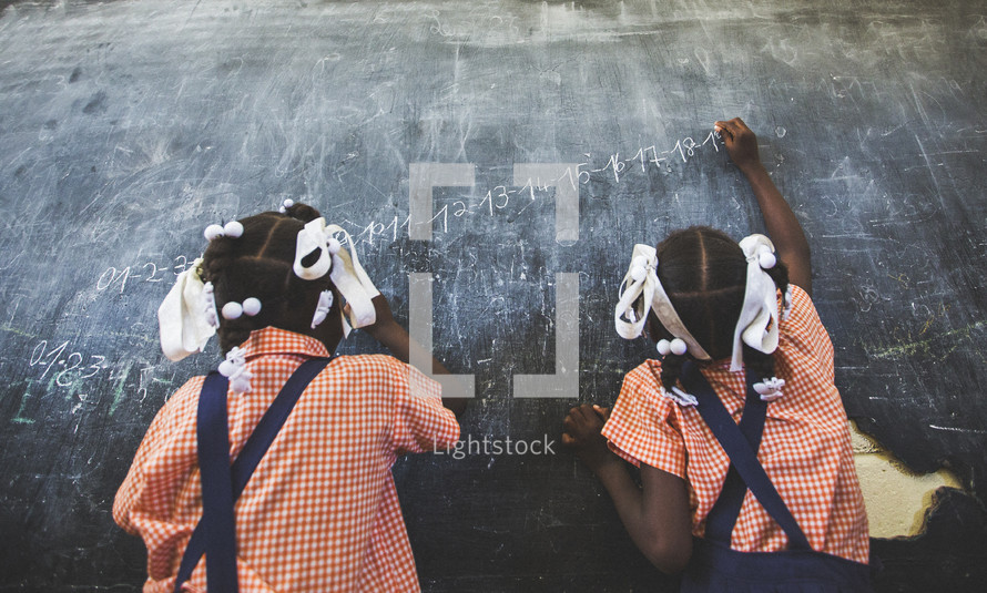 young African-American girls drawing on a blackboard
