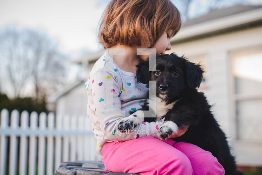 toddler girl hugging a puppy