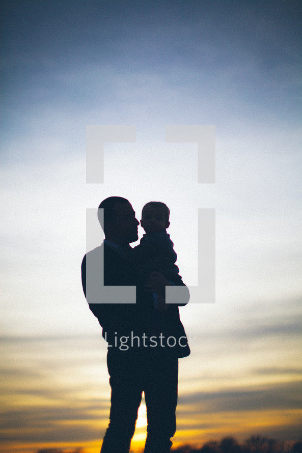silhouette of a father holding his toddler son