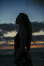 side profile of a woman standing on a beach at dusk