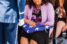 crying widow holding a folded American flag