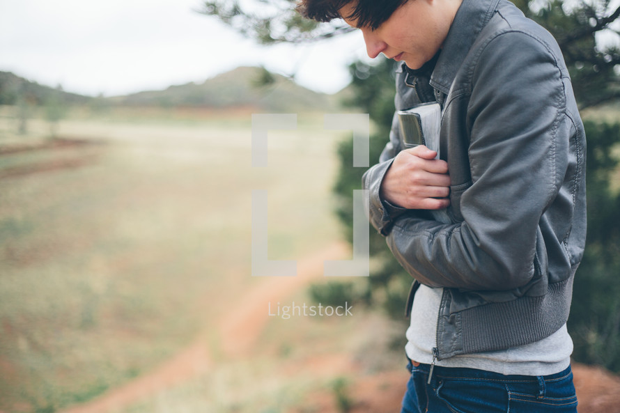 Woman standing outside clutching a Bible while praying.