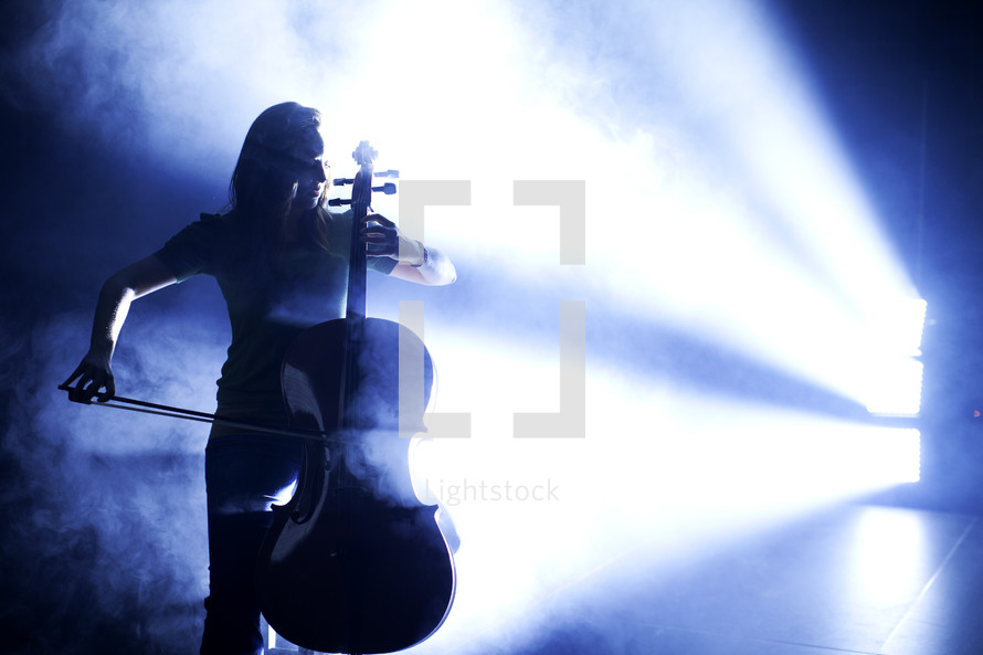 woman in a spot light playing a cello