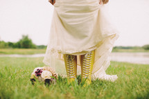 A bride pulling up her dress to show yellow lace up boots