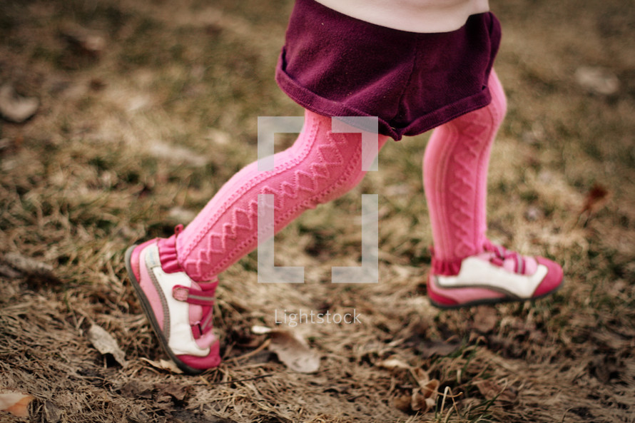 A little girl running in pink tights.