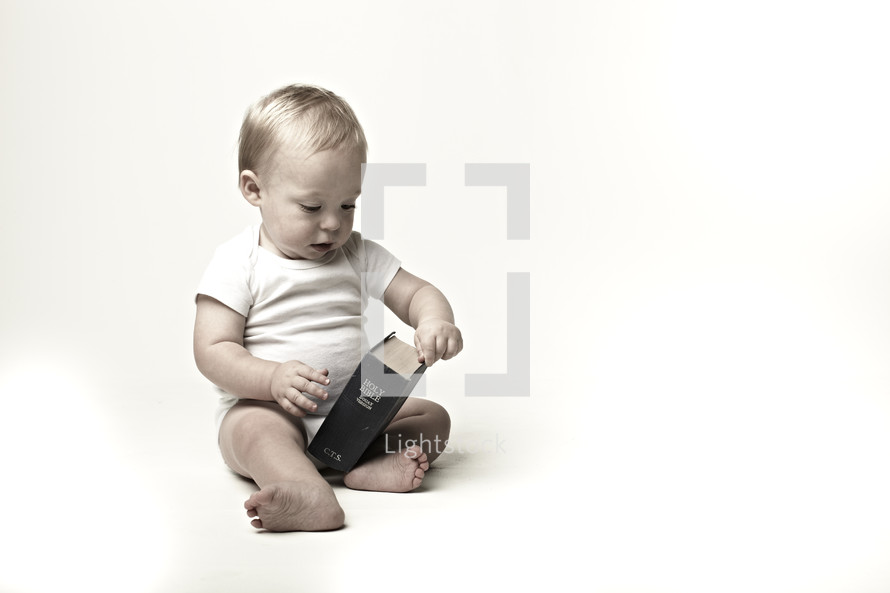 A toddler looks curiously at the Bible