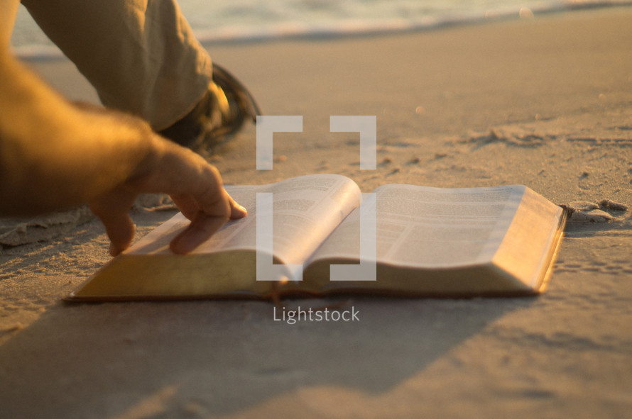 man pointing to scripture in the Bible sitting on a beach