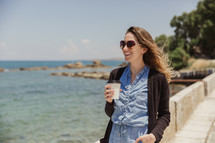 woman walking holding a coffee cup outdoors along the coast in Greece