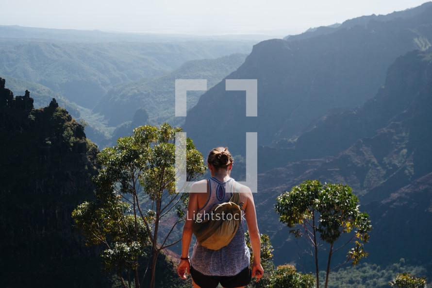 a woman exploring a mountainous landscape
