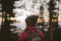 a woman standing outdoors with a backpack