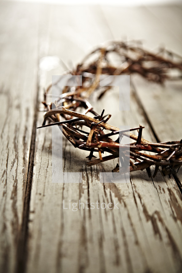 A crown of thorns on white washed wood planks.
