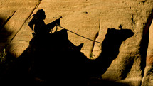 Man traveling on a journey riding a camel