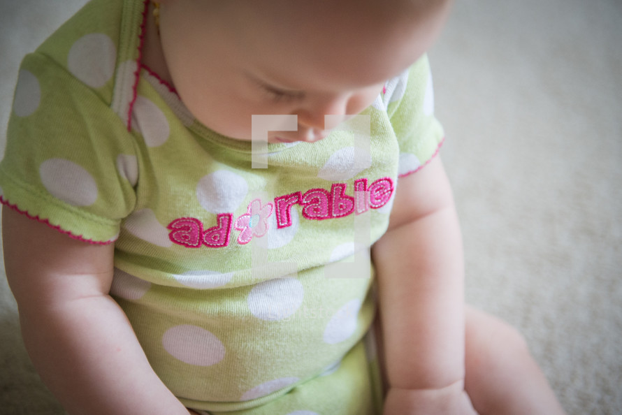 an infant in a onesie looking down