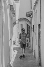 man walking down a narrow alley in Greece