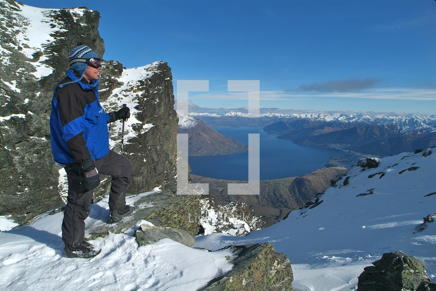 man standing on top of snow capped mountain ridge overlooking river