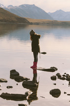 A girl standing on a rock at the edge of a lake in the mountains.