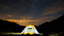 glowing tent under stars in the night sky