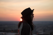 side profile of a woman in a hat at sunset