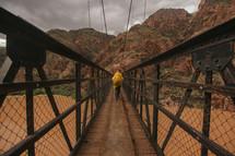 crossing a footbridge over a muddy river