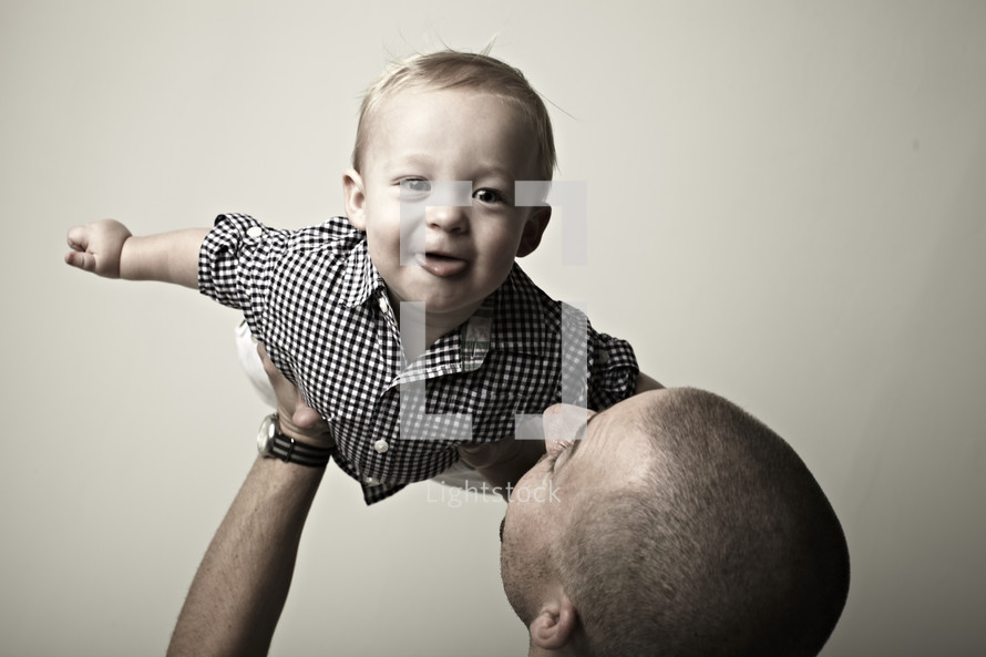 Small boy being lifted up by his young adult father.