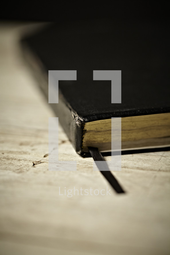 Black Bible and bookmark resting on a table