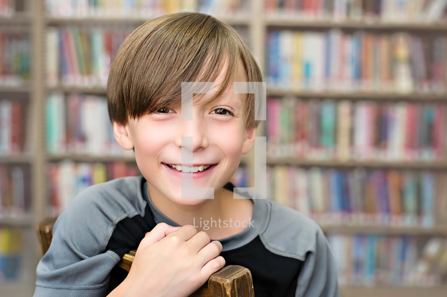Smiling boy sitting in a chair in a library.