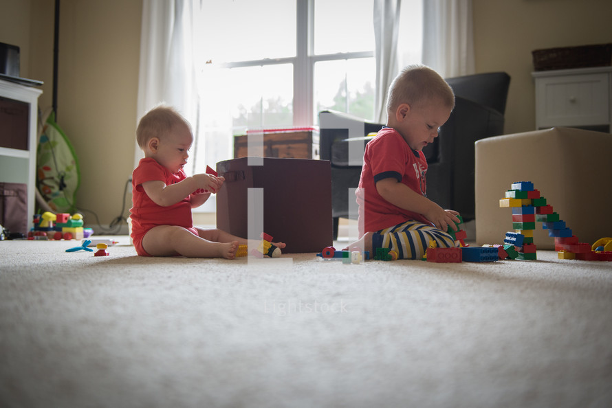 toddler boys playing with building blocks