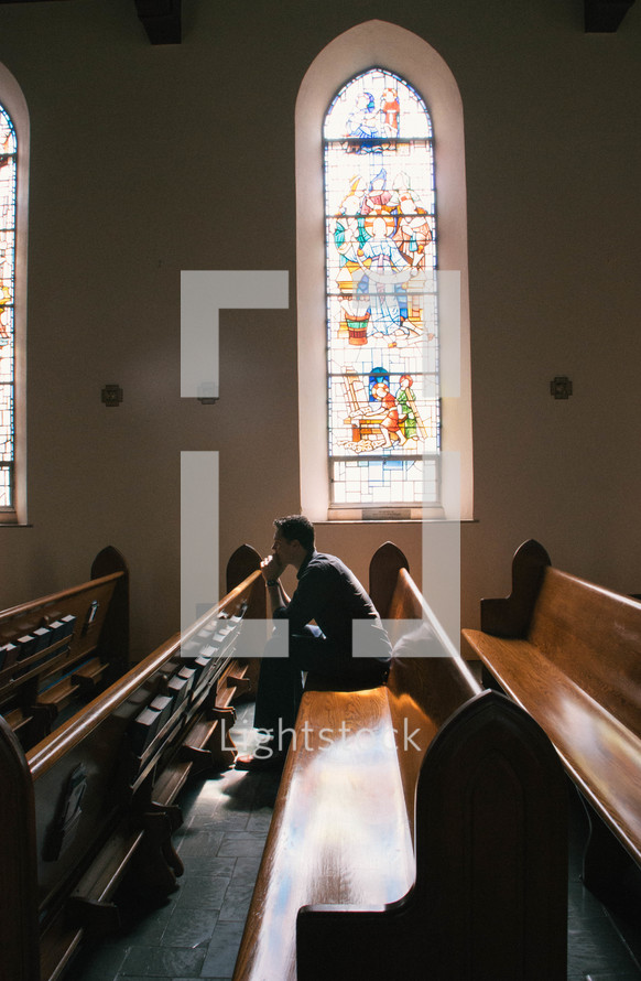 a man sitting in an empty church praying