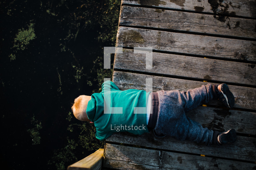 toddler boy leaning over a pier looking at lake water