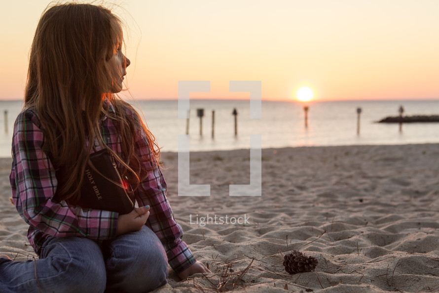 young girl sitting in the sand on the beach holding her bible at sunset